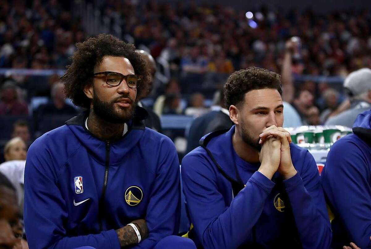 Injured Willie Cauley-Stein #2 and Klay Thompson #11 sit on the bench during their game against the Los Angeles Lakers at Chase Center on October 05, 2019 in San Francisco.