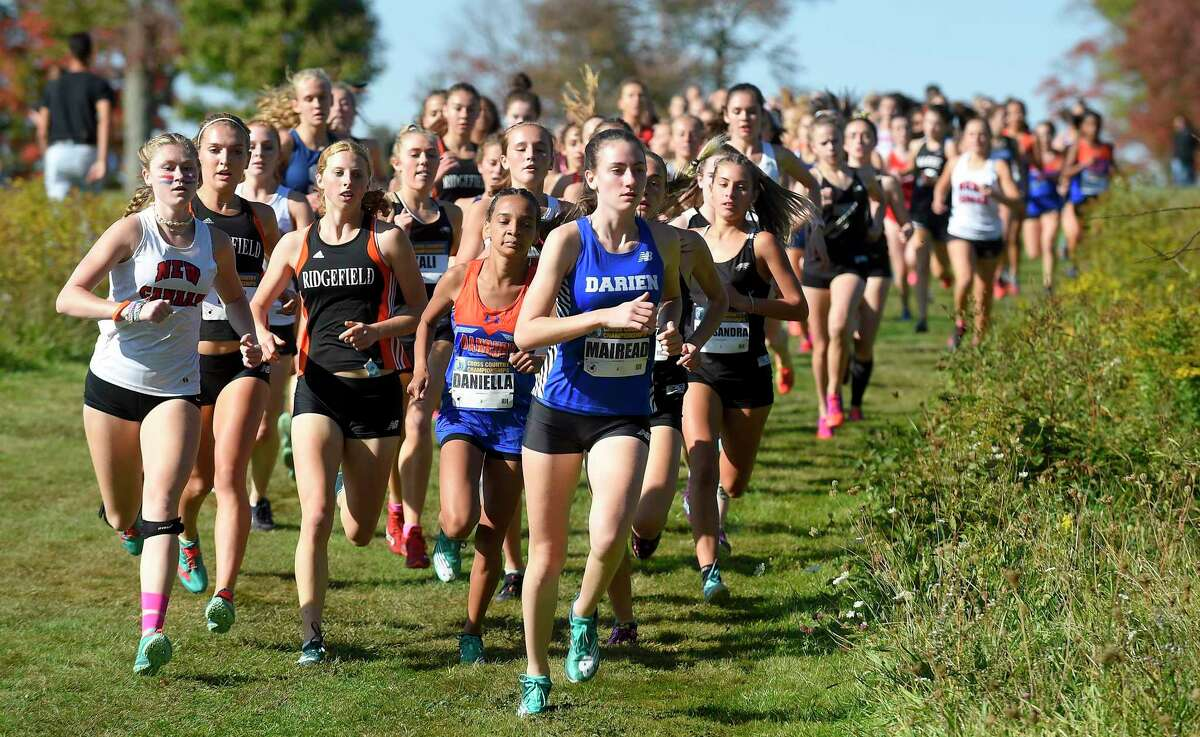 Darien sophomore Mairead Clas leads a pack of runners around a turn during the FCIAC Cross Country Championships at Waveny Park in New Canaan on Tuesday.