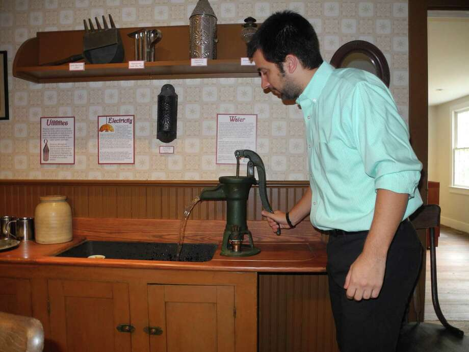 Associate curator Nick Foster demonstrates a water pump in the Wilton Historical Society's 1910 kitchen. Photo: Jeannette Ross / Hearst Connecticut Media / Wilton Bulletin