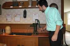 Associate curator Nick Foster demonstrates a water pump in the Wilton Historical Society's 1910 kitchen.