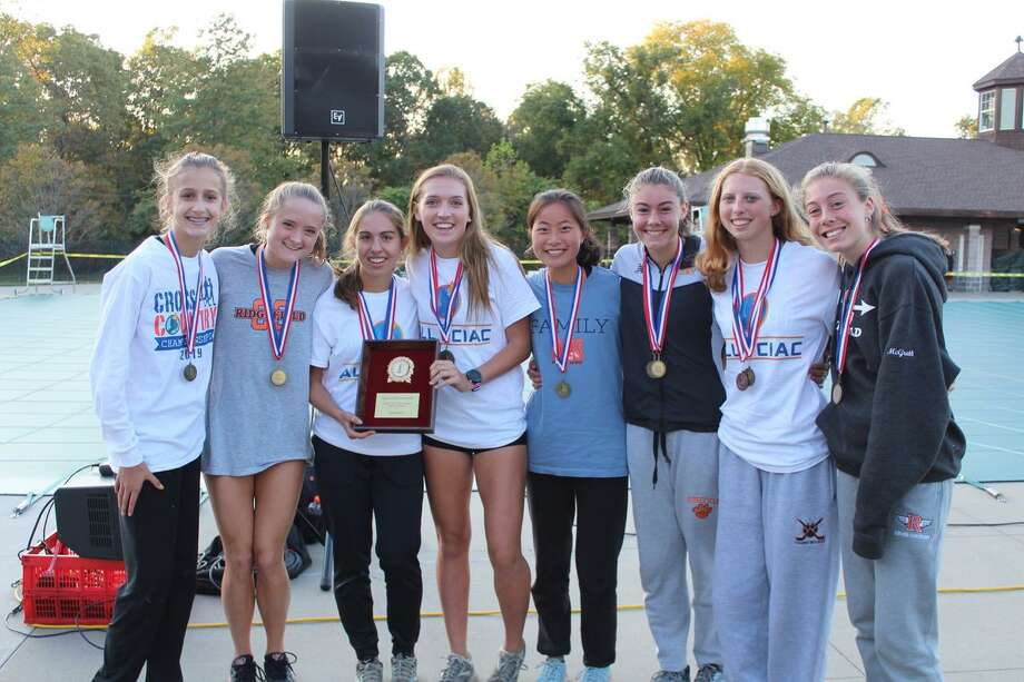 The Ridgefield girls cross country team celebrates its FCIAC championship. Photo: Contributed Photo / RHS Cross Country Program