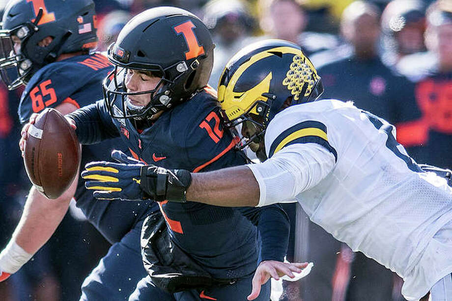 Illinois quarterback Matt Robinson (12) is taken down by Michigan's Josh Ache (6) in Saturday in Champaign. Photo: Holly Hart | AP Photo