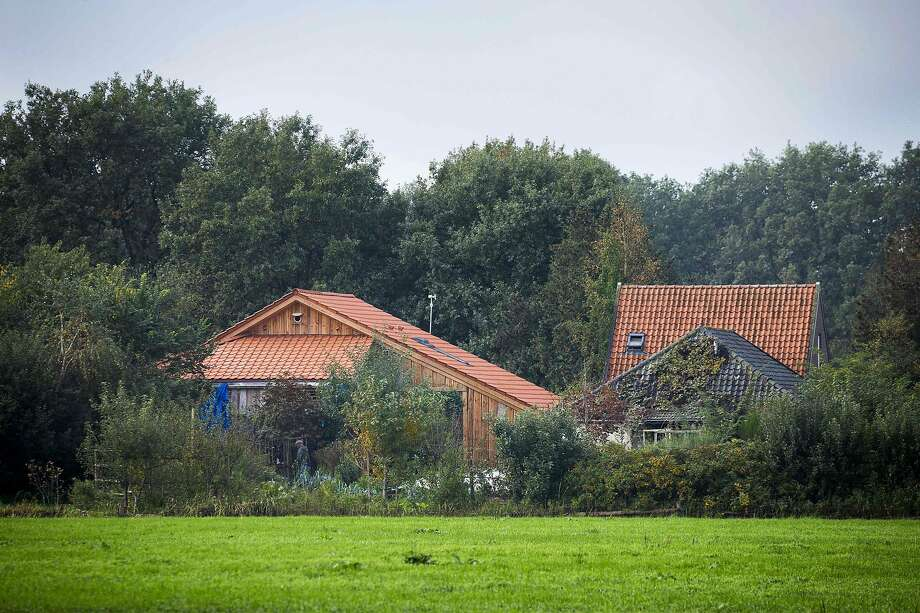 """A plain clothes policeman inspects the farmhouse in a remote area of northern Netherlands' province of Drenthe, near the village of Ruinerwold, on October 16, 2019 a day after Dutch police discovered a hidden staircase behind a cupboard leading to a cellar where a man and five others believed to be his children aged between 18 and 25 were hidden and reportedly spent years """"waiting for the end of time"""", officials said. - Local media said the family were found after one of the sons went to a nearby pub in a confused state, drank five beers and then asked for help, saying he had not been outside for nine years. Police arrested a 58-year-old man at the scene for failing to cooperate with the investigation, but he was not the father. Many questions were unanswered  and police are investigating """"All scenarios"""". """"At this point we cannot give further information,"""" local police said. (Photo by Vincent Jannink / ANP / AFP) / Netherlands OUT (Photo by VINCENT JANNINK/ANP/AFP via Getty Images) Photo: Vincent Jannink, ANP/AFP Via Getty Images"""