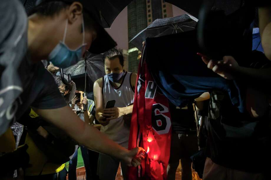 Demonstrators set a Lebron James jersey on fire during a rally at the Southorn Playground in Hong Kong, Tuesday, Oct. 15, 2019. Protesters in Hong Kong have thrown basketballs at a photo of LeBron James and chanted their anger about comments the Los Angeles Lakers star made about free speech during a rally in support of NBA commissioner Adam Silver and Houston Rockets general manager Daryl Morey, whose tweet in support of the Hong Kong protests touched off a firestorm of controversy in China. Photo: Mark Schiefelbein / Associated Press / Copyright 2019 The Associated Press. All rights reserved