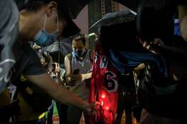 Demonstrators set a Lebron James jersey on fire during a rally at the Southorn Playground in Hong Kong, Tuesday, Oct. 15, 2019. Protesters in Hong Kong have thrown basketballs at a photo of LeBron James and chanted their anger about comments the Los Angeles Lakers star made about free speech during a rally in support of NBA commissioner Adam Silver and Houston Rockets general manager Daryl Morey, whose tweet in support of the Hong Kong protests touched off a firestorm of controversy in China.