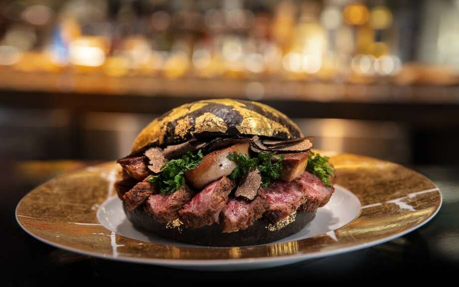 The Post Oak Hotel in Uptown has created a burger called The Black Gold, priced at $1,600. The wagyu burger, topped with foie gras and black truffles comes on a 24-karat gold flecked bun that is infused with caviar; burger is served with a bottle of 2006 Dom Perignon champagne. Photo: The Post Oak