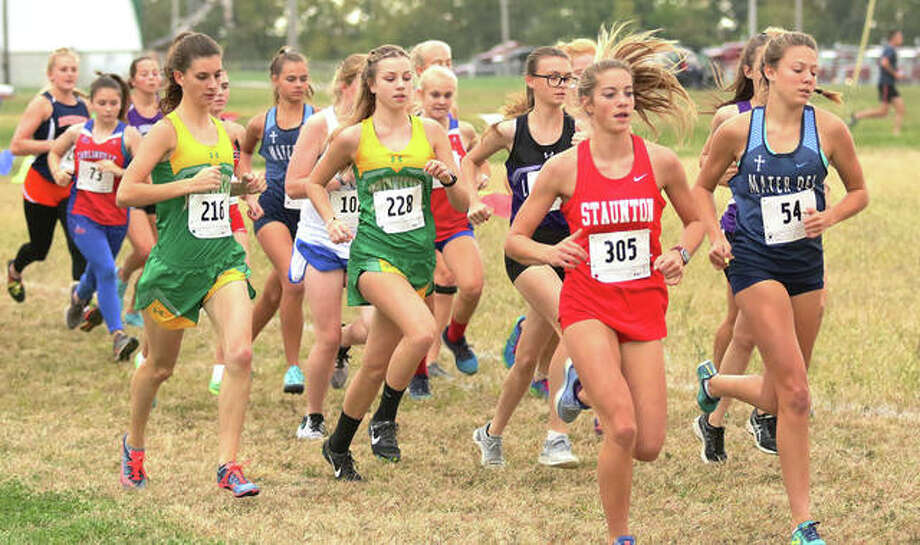 Staunton's Brooke Kinder (305) and Southwestern's Laina Wilderman (216) and Allison Brown (218) run out with other runners at the start of the girls race at the Carlinville Invitational cross country meet on Monday at the Macoupin County Fairgrounds in Carlinville. Photo: Greg Shashack / The Telegraph