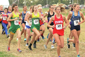 Staunton's Brooke Kinder (305) and Southwestern's Laina Wilderman (216) and Allison Brown (218) run out with other runners at the start of the girls race at the Carlinville Invitational cross country meet on Monday at the Macoupin County Fairgrounds in Carlinville.