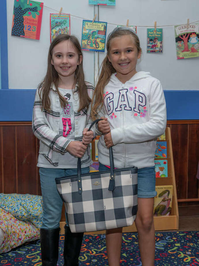 The YWCA of Alton will offer 30 great bags in this year's annual purse raffle, along with some special gifts, during November. Pictured with a checkered bag are Ella Chapman and Avery Hammond. Pictured with a red purse are Genesis Brumfield and Lilyanna Nicholson. For more details, visit www.altonywca.com or the YWCA of Alton Facebook page.