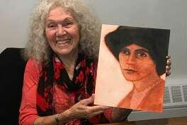 Artist Suzanne Benton with her portrait of Alice Paul.