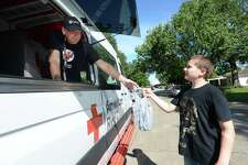 Allan Sherman of Longview, TX, hands a bag of cold waters to Carmine Plaia as his wife Janet boxes meals during a stop on Broadway off of S. 27th St. as they make their way throughout flooded Beaumont neighborhoods where residents were in the process of gutting their damaged homes Tuesday. The couple started volunteering a year and a half ago after Allen retired. The devastation caused by Tropical Storm Harvey two years ago is what drew them to become Red Cross volunteers. The couple got to Beaumont Tuesday morning after stopping in Houston yesterday. They have burgers, chips, water and snacks available to those in need. The Shermans aren't sure how long they will be in Beumont, but will at least be here through Wednesday trying to make it to as many affected areas as possible. Photo taken Tuesday, September 24, 2019 Kim Brent/The Enterprise