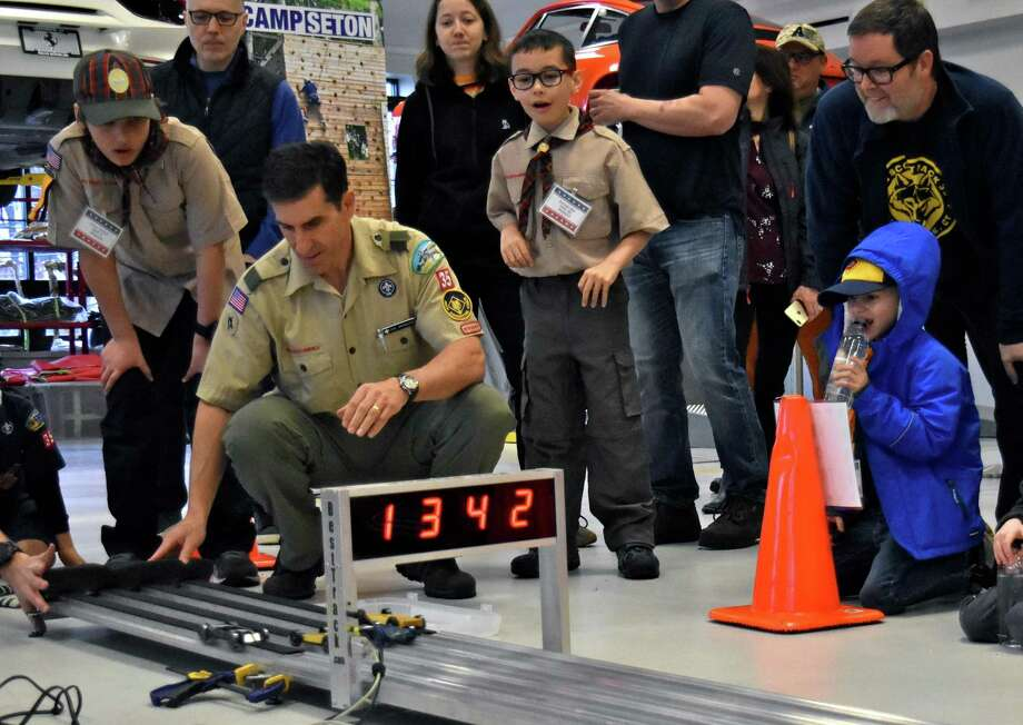 Cub Scouts and their parents watch the finish line at the 2019 Pinewood Derby Championship at Miller Motorcars. Adults will have their chance to race on November 9 at the Pinewood Derby Challenge. Photo: Contributed Photo