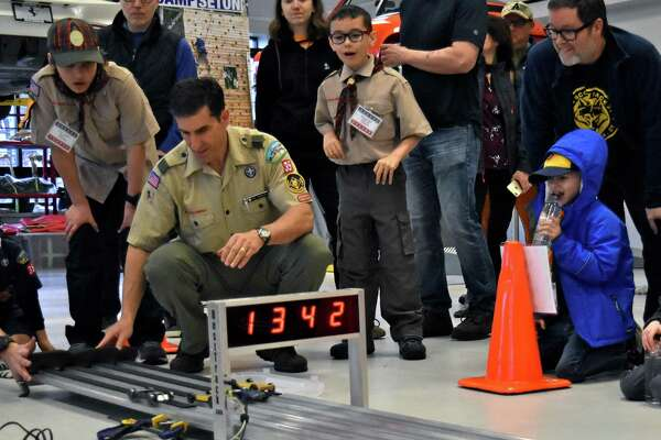 Cub Scouts and their parents watch the finish line at the 2019 Pinewood Derby Championship at Miller Motorcars. Adults will have their chance to race on November 9 at the Pinewood Derby Challenge.