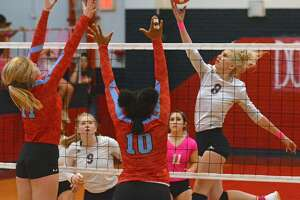 Plainview's Lexie Bennett attempts to tap the ball away from Lubbock Monterey defenders Khristian Butler (10) and Madeline Stephens during their District 3-5A volleyball match on Tuesday in the Dog House. Also pictured for Plainview are Haley Curtis (9) and Emily Sigala (11).