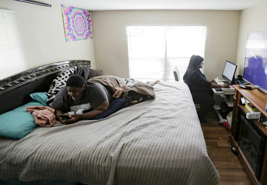 Jessica Byas-Lurgio works on homework for her master's degree as her son Anthony Jones, 19, hangs out on her bed. Photo: Elizabeth Conley/Staff Photographer