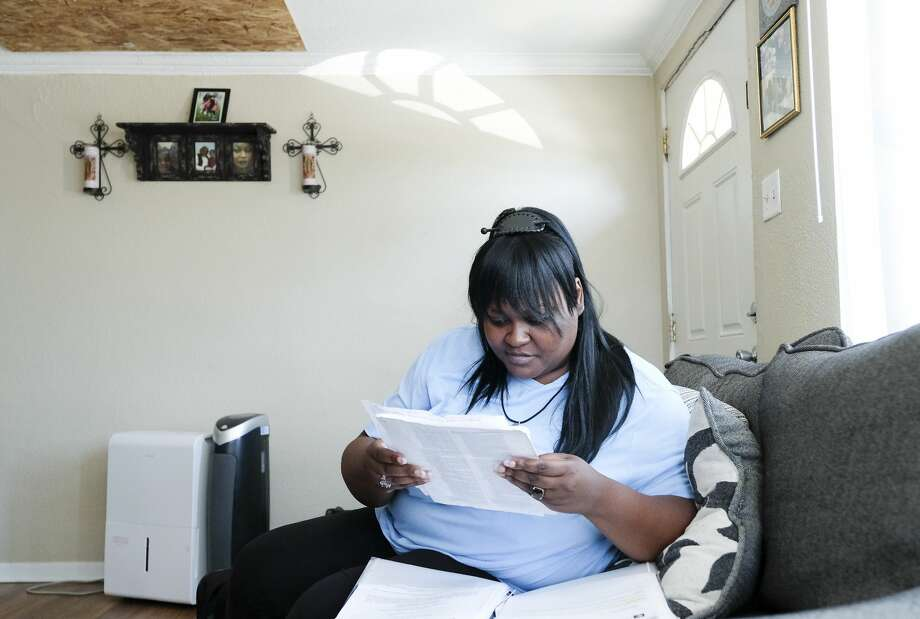 Jessica Byas-Lurgio looks over medical notes while recounting when she lost custody of her half-siblings in her Joliet, Ill., home. Photo: Elizabeth Conley/Staff Photographer