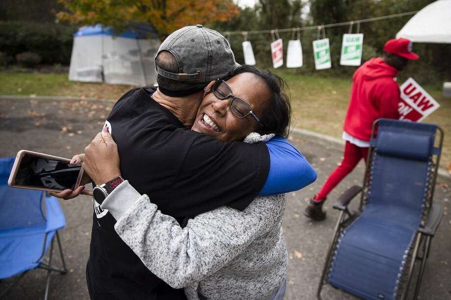Workers Richard Rivera and Robin Pinkney react to the tentative agreement with General Motors in Langhorne, Pa. The strike is still on for the moment, though, which is why Ryan Piper continues to picket, below. Photo: Photos By Matt Rourke / Associated Press