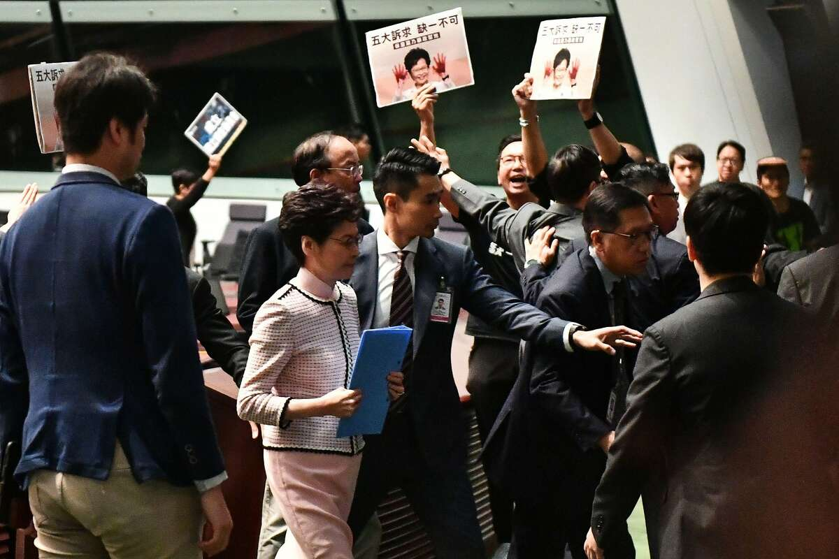 TOPSHOT - Hong Kong's Chief Executive Carrie Lam (2nd L) leaves the chamber for a second time while trying to give her annual policy address as she is heckled by pro-democracy lawmakers (at background) at the Legislative Council (Legco) in Hong Kong on October 16, 2019. - Hong Kong leader Carrie Lam was to unveil a closely watched State of the Union-style speech on October 16 aimed at winning hearts and minds after four months of seething pro-democracy protests. (Photo by Anthony WALLACE / AFP) (Photo by ANTHONY WALLACE/AFP via Getty Images)