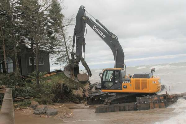 Swidorski Brothers Excavating's equipment works on fortifying the shoreline home owned by Rochelle Radlinski on Lakeshore Road by placing large rocks to protect it from washing into Lake Michigan. (Michelle Graves/News Advocate)