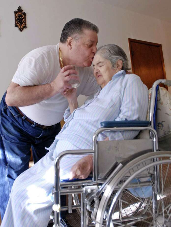 A caregiver kisses his mother who has Alzheimer's disease.
