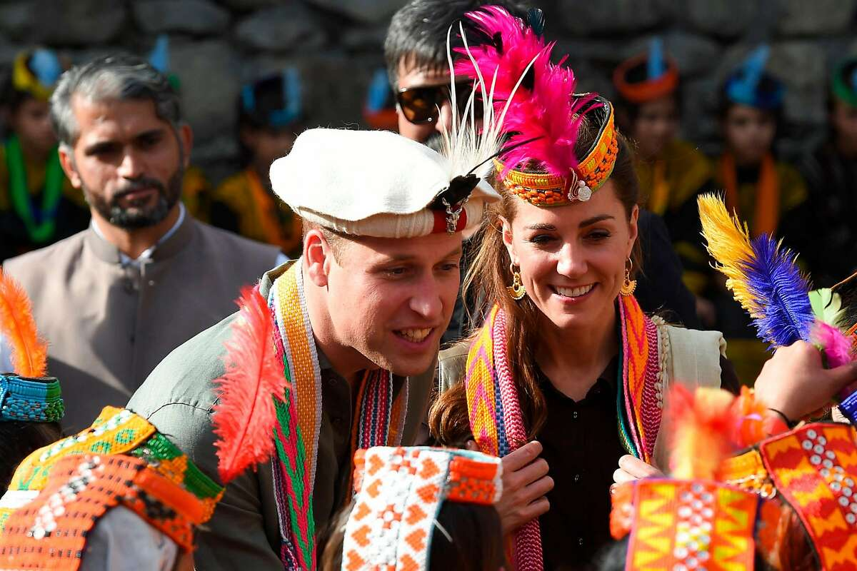 Britain's Prince William (C), Duke of Cambridge and his wife Catherine (R), Duchess of Cambridge, chat with members of the Kalash tribe during their visit to the�Bumburate Valley in Pakistan northern Chitral District on October 16, 2019. - Prince William and his wife Kate flew near the Afghan border to visit a remote Hindu Kush glacier on October 16, after a morning spent trying on feathered traditional caps and luxurious shawls in Pakistan's mountainous north. (Photo by FAROOQ NAEEM / AFP) (Photo by FAROOQ NAEEM/AFP via Getty Images)