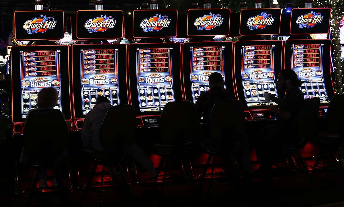 FILE - In this July 23, 2019 file photo, slot machine players are silhouetted on the floor of the casino at the WinStar World Casino and Resort in Thackerville, Okla. For the last 15 years, casino gambling has been a financial boon for Oklahoma and many of the Native American tribes located there. (AP Photo/Sue Ogrocki)