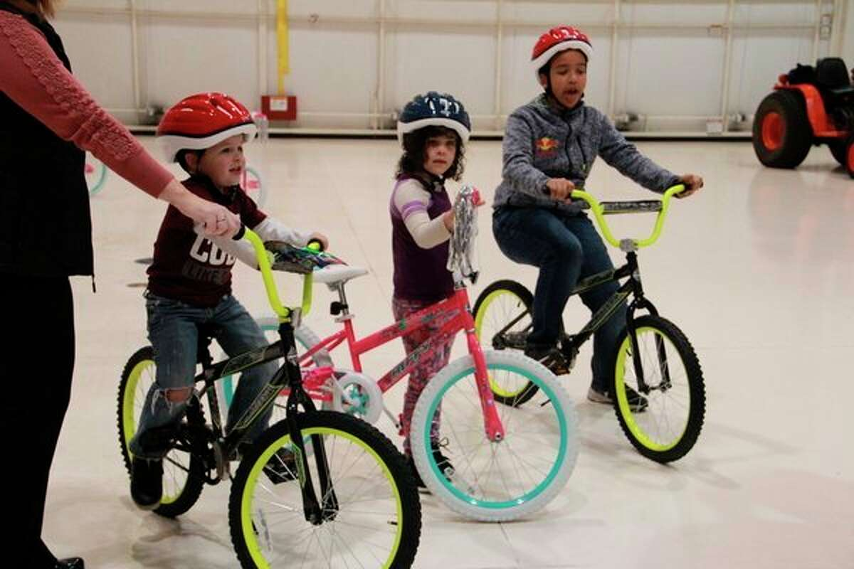 """Siblings,Blayze Moller, 4,Zailya Romine, 6, andMykal Henderson, 11,were able to pick out their own bicycles Tuesday. The bikes were built byAero Med of Grand Rapids and North Flight Aero Med of Traverse Cityteams during their annual """"Safety Day"""" workshop.(Pioneer photo/Alicia Jaimes)"""