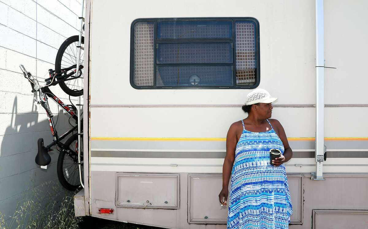 """Lorene Briley, 45, stands outside her RV as she smokes at the site of a new pilot RV Safe Parking program at 771 71st. Ave. in Oakland, Calif., on Friday, June 21, 2019. She and her 18-year-old son moved to the location the day prior. """"I do feel safe, there's security,"""" Briley said. """"I don't think people will steal from me like they did on the street, so I'm enjoying it."""""""