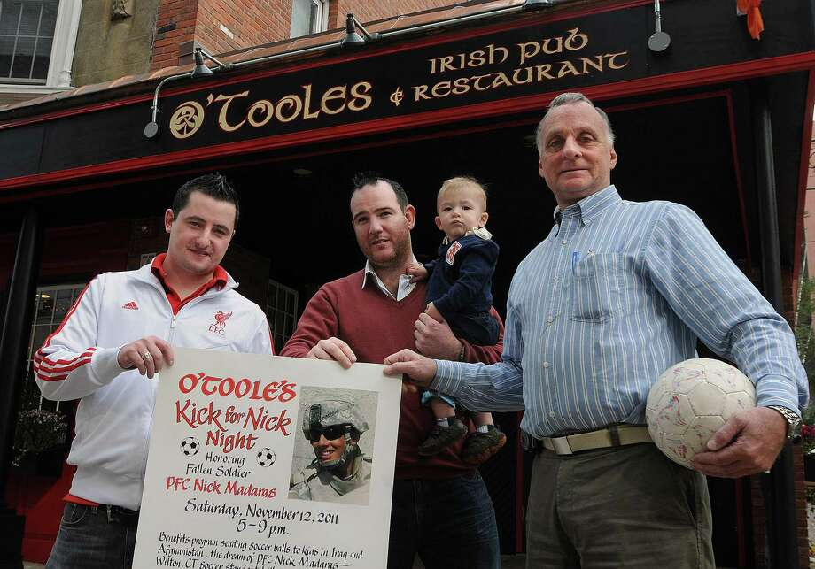 In this file photo, Bill Madaras, right, father of fallen army soldier Nick Madaras, and the owners of O'Toole's Pub, Colin O'Toole, left and Damian Cashman (With then 1-year-old son, Luke Cashman) are holding a fundraiser in Nick's name. Nick was very involved with helping Iraqi children before he was killed. In his name, thousands of soccer balls have been donated and sent to children in Iraq. Photo: Peter Casolino / Hearst Connecticut Media File Photo