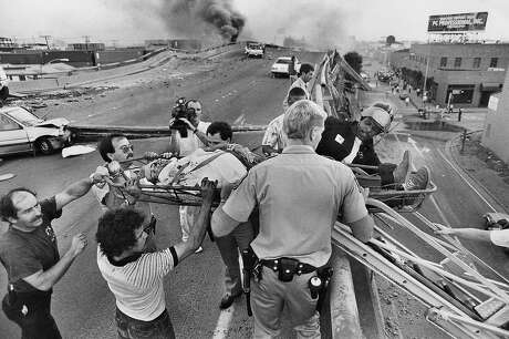 The Cypress Structure in Oakland collapsed during the Loma Prieta quake, killing 42 people who were trapped in their vehicles. Rescue personnel atop the stucture scrambled to carry out the injured. Photo: Michael Macor / Associated Press 1989