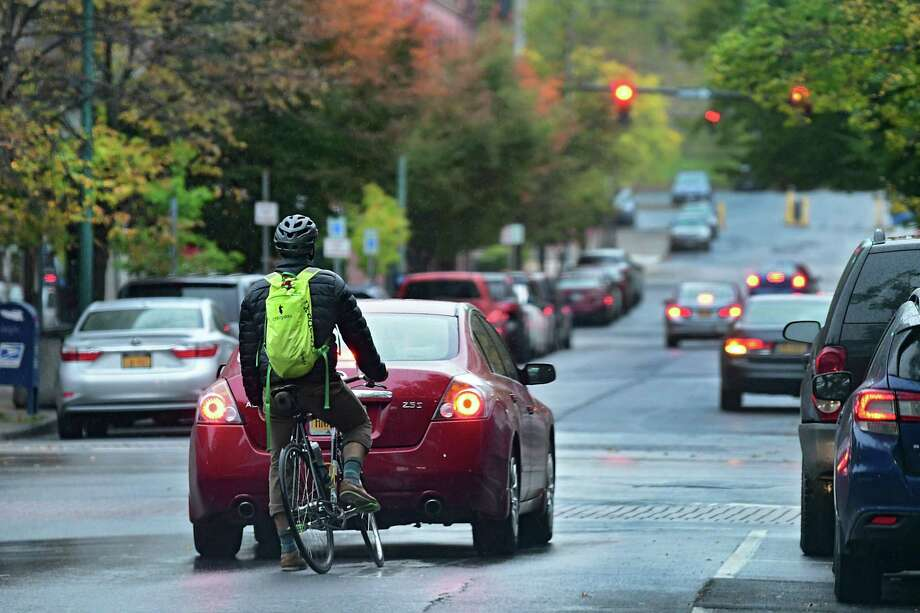 A bicyclist waits behind a car at a red light at Fulton and 4th Streets during a light rain on Wednesday, Oct. 16, 2019 in Troy, N.Y. (Lori Van Buren/Times Union) Photo: Lori Van Buren, Albany Times Union