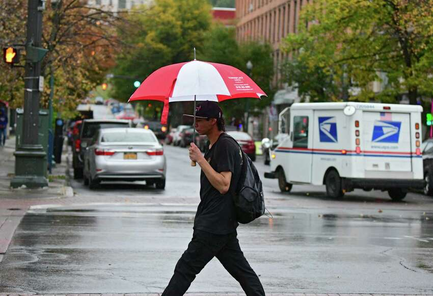 A pedestrian crossing at Fulton and 4th Streets uses an umbrella during a light rain on Wednesday, Oct. 16, 2019 in Troy, N.Y. (Lori Van Buren/Times Union)