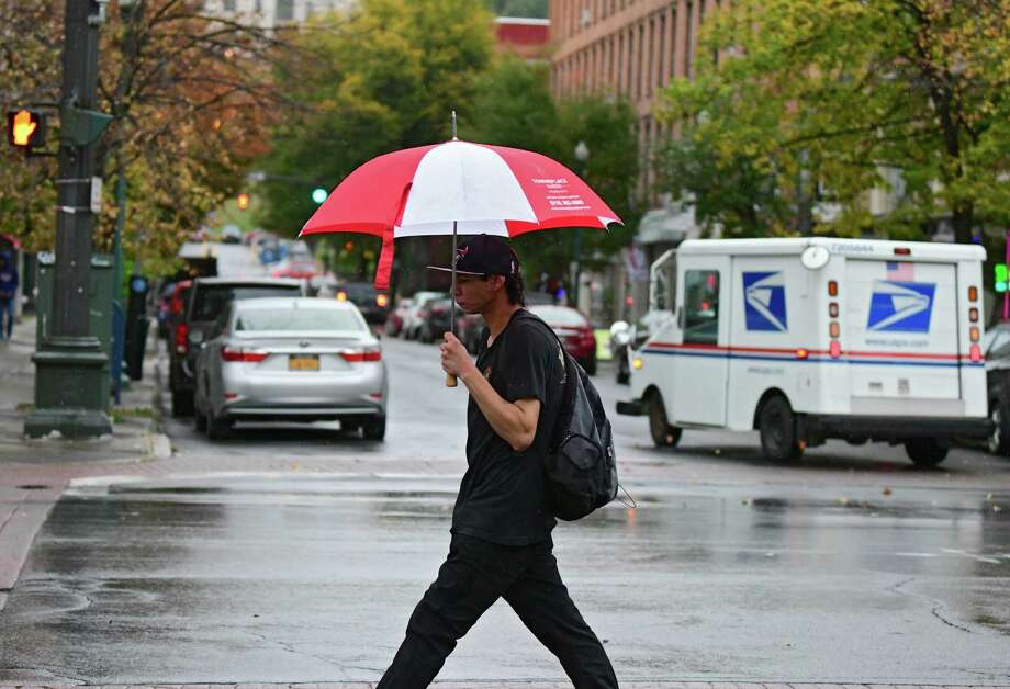 A pedestrian crossing at Fulton and 4th Streets uses an umbrella during a light rain on Wednesday, Oct. 16, 2019 in Troy, N.Y. (Lori Van Buren/Times Union) Photo: Lori Van Buren, Albany Times Union