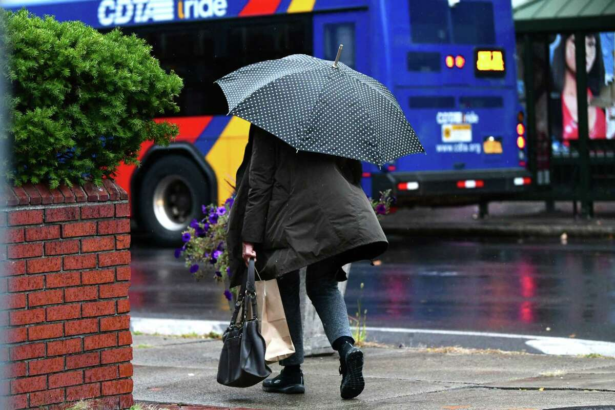 Wind blows the jacket of a woman walking near Fulton and 4th Streets during a light rain on Wednesday, Oct. 16, 2019 in Troy, N.Y. (Lori Van Buren/Times Union)
