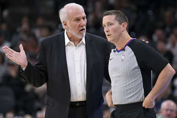 San Antonio Spurs head coach Gregg Popovich, left, talks to referee Nick Buchert during the first half of an NBA preseason basketball game against the New Orleans Pelicans, Sunday, Oct. 13, 2019, in San Antonio. (AP Photo/Darren Abate)