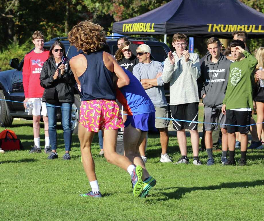 Wilton's Davis Cote, left, helps Danbury's Aidan Byrne across the finish line at the FCIAC championships on Tuesday at Waveny Park in New Canaan. Photo: Mary Reingruber / Contributed Photo