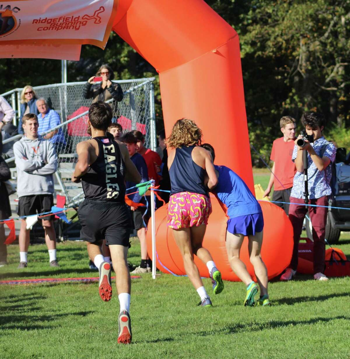 Wilton's Davis Cote, left, helps Danbury's Aidan Byrne across the finish line at the FCIAC championships on Tuesday at Waveny Park in New Canaan.