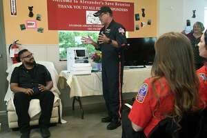 Alexander Coreas, 27, left, listens as Houston Methodist Life Flight Paramedic Rob Altripaldi describes his team's part in the rescue of Coreas after he was struck by lightning on Oct. 3 in the parking lot of Stuebner Airline Veterinary Hospital in Spring at a Celebration of Life Saved at the hospital on Oct. 15, 2019.