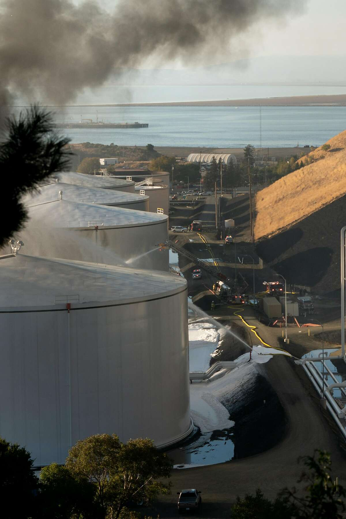 Fire crews work to extinguish flames after an explosion at NuStar energy facility in Crockett, Calif. on Tuesday, Oct. 15, 2019.