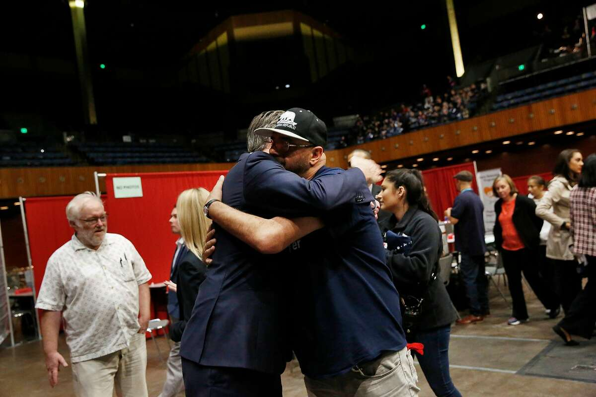 Governor Gavin Newsom (l to r) and Richard Oliva, Reading Glasses volunteer, hug after Oliva thanked Newsom for his support of housing for the homeless while Newsom toured Project Homeless Connect at the Bill Graham Civic Auditorium on Wednesday, October 16, 2019 in San Francisco, Calif. Oliva said he now has permanent housing and attributes it to Newsom's support of housing.
