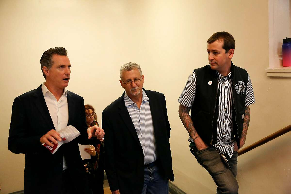Governor Gavin Newsom (l to r), Jeff Kositsky, director Department of Homelessness and Supportive Housing and Mark Mazza, SFHOT lead clinical supervisor of outreach, speak as Governor Newsom tours Project Homeless Connect at the Bill Graham Civic Auditorium on Wednesday, October 16, 2019 in San Francisco, Calif.