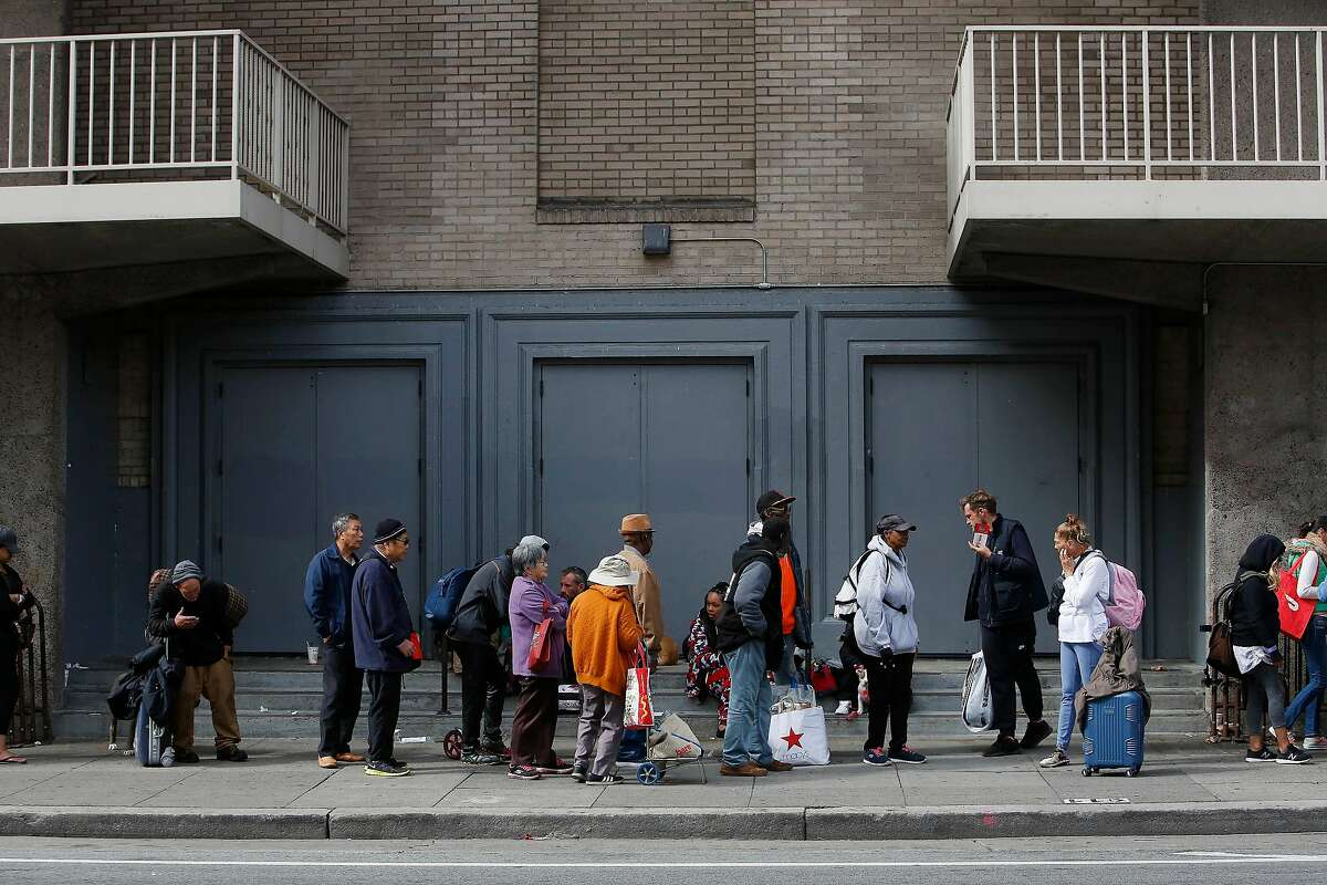 People line up on Larkin Street outside the Bill Graham Civic Auditorium to attend Project Homeless Connect on Wednesday, October 16, 2019 in San Francisco, Calif.