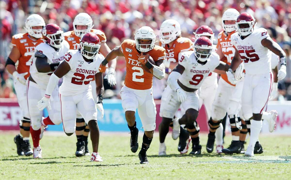 Texas quarterback Roschon Johnson (2) runs up the field for a big play as the Oklahoma defense gives chase during the second half in the Red River Showdown at the Cotton Bowl in Dallas on Saturday, Oct. 12, 2019. Oklahoma won, 34-27. (Vernon Bryant/Dallas Morning News/TNS)