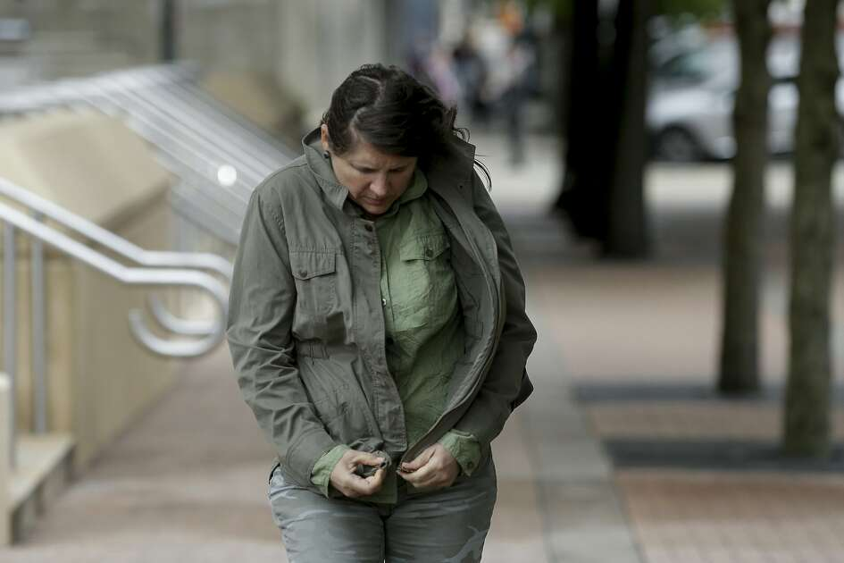 Lara Anne zips up her jacket as a gust of wind hits her outside the Harris County Courthouse Wednesday, Oct. 16, 2019, in Houston. A cold front and scattered rains are affecting the greater Houston area.