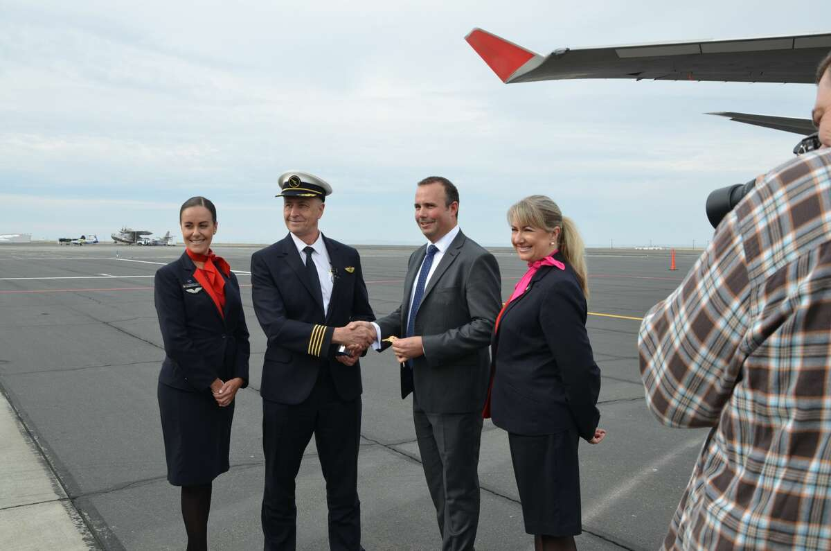Qantas Airways Captain Robert Nelson hands over the keys to the airplane to Rolls-Royce Director of Development and Experimental Engineering Gareth Hedicker during a ceremony at Moses Lake, WA.