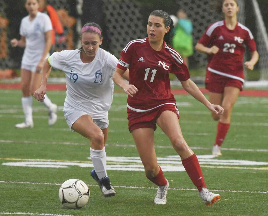 Darien's Kate Bellissimo (19) and New Canaan's Riana Afshar (11) battle for the ball in the rain during a girls soccer game at New Canaan's Dunning Field on Wednesday, Oct. 16, 2019. Photo: Dave Stewart / Hearst Connecticut Media / Hearst Connecticut Media