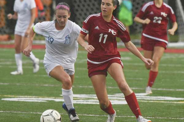 Darien's Kate Bellissimo (19) and New Canaan's Riana Afshar (11) battle for the ball in the rain during a girls soccer game at New Canaan's Dunning Field on Wednesday, Oct. 16, 2019.