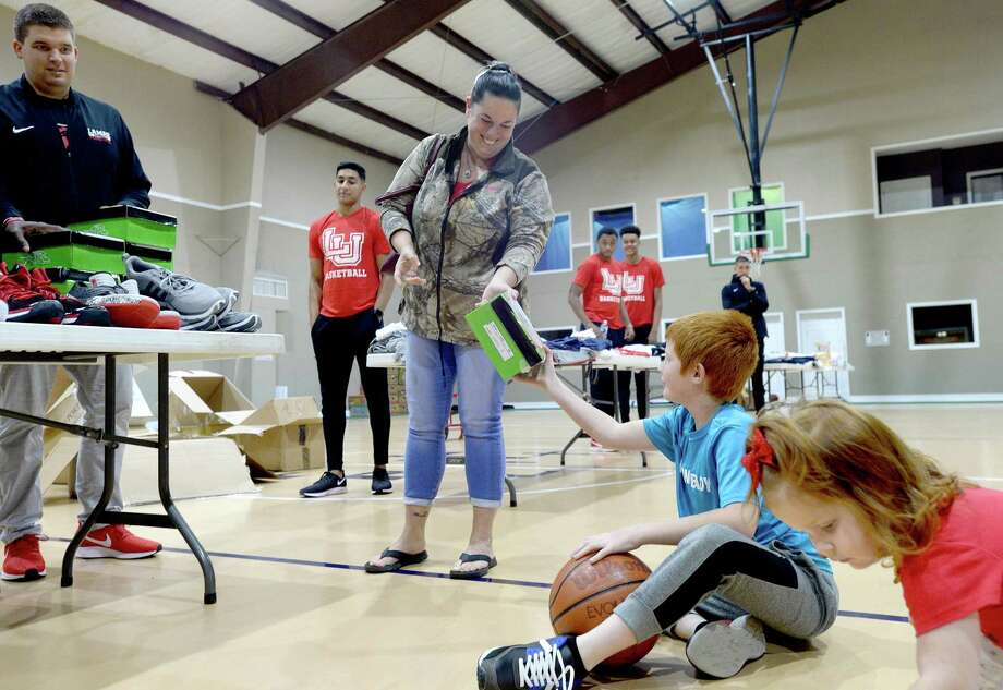 Tammy Ray hands her son Gage the box for his new gym shoes as they and Evangeline Ray stop to pick up needed items during Lamar basketball's clothing and shoe give-away to those affected by flooding at First Baptist Church in Hamshire Wednesday. Photo taken Wednesday, October 16, 2019 Kim Brent/The Enterprise Photo: Kim Brent / The Enterprise / BEN