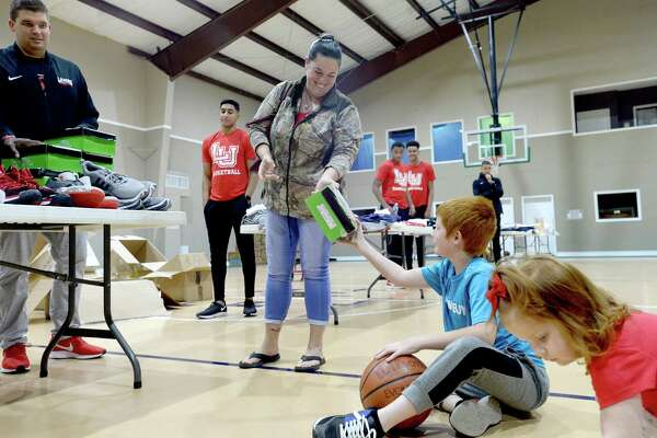 Tammy Ray hands her son Gage the box for his new gym shoes as they and Evangeline Ray stop to pick up needed items during Lamar basketball's clothing and shoe give-away to those affected by flooding at First Baptist Church in Hamshire Wednesday. Photo taken Wednesday, October 16, 2019 Kim Brent/The Enterprise