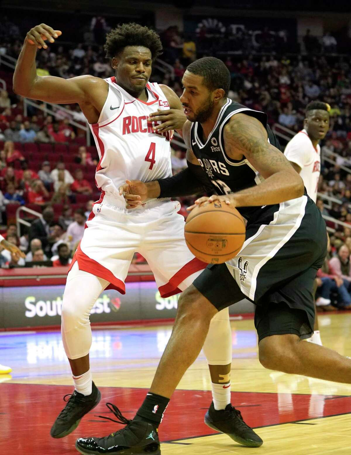 San Antonio Spurs LaMarcus Aldridge goes to the basket and draws a foul from Houston Rockets Danuel House Jr. during the first half of NBA game at Toyota Center Wednesday, Oct. 16, 2019, in Houston.